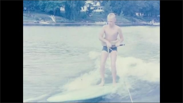 1960s: Lake.  Homes.  Young man water skis on surfboard.  Boy lets go of rope and falls into water.