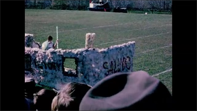 1960s: Football field.  Trucks and tractors pull floats.  People ride in convertibles.