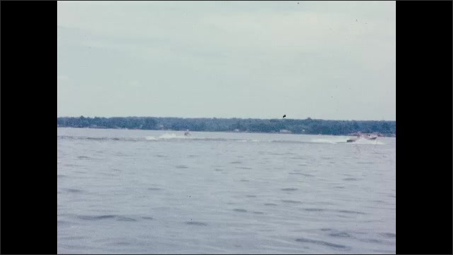 1960s: Lake.  Boat tows water skiers.  People in rowboat.  Man and woman float on tubes.