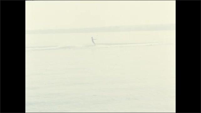 1960s: Lake.  Homes.  Boat pulls water skier.