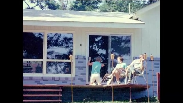 1960s: UNITED STATES: people sunbathe on jetty. Lady cleans glass door of bungalow. Motor boat on water.