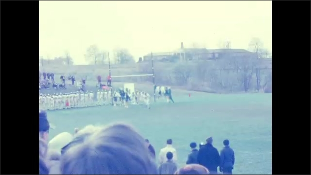 1960s: UNITED STATES: mascot and girls clap. Girl with pom poms. American football players run onto pitch.