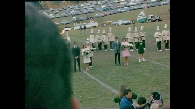 1960s: UNITED STATES: lady receives flowers during carnival event on field. Band plays on pitch.