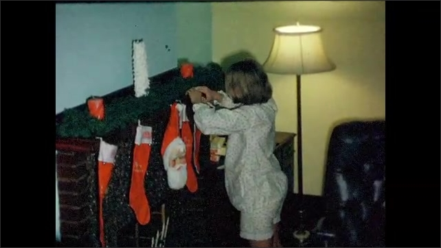 1960s: UNITED STATES: children hang stockings on mantel piece. Christmas presents on floor and in stockings.