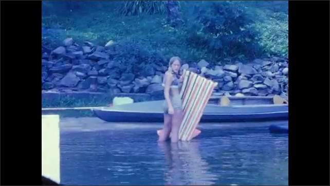 1960s: UNITED STATES: boat on lake. Girl paddles tire on water. Man outside bungalow in garden.