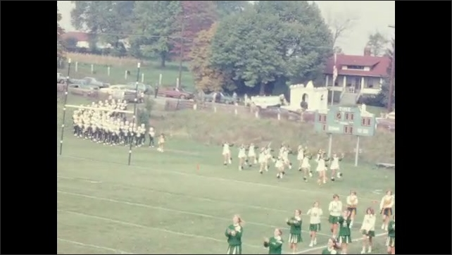 1960s: UNITED STATES: cheerleaders and band perform for crowd before match. Carnival floats on soccer pitch.