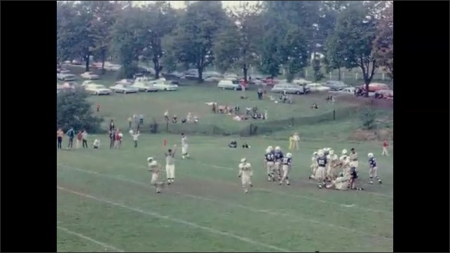 1960s: UNITED STATES: American football game on pitch at school. Girl cheerleading