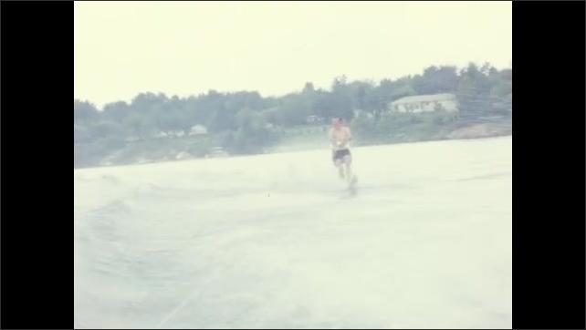 1960s: UNITED STATES: two men water ski behind boat on lake.