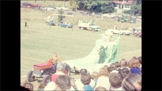 1960s: UNITED STATES: students sit on cars and floats at end of year celebration.