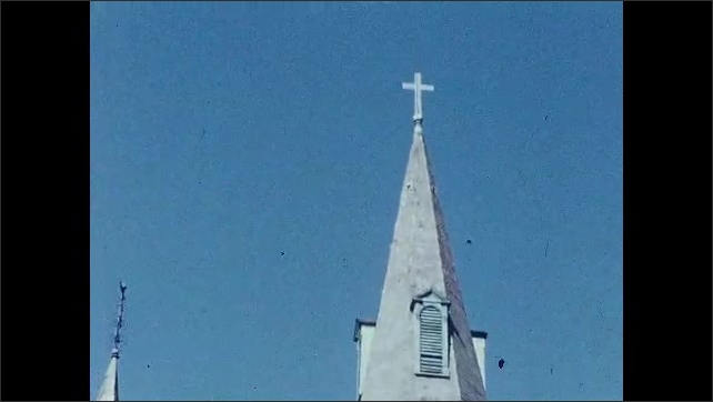 1950s: CARIBBEAN: people walk past building. Clock on building. Church tower. Gardens by building. Cross on tower
