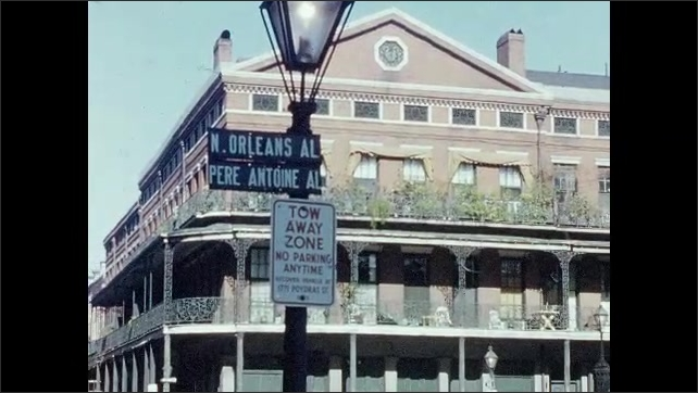 1950s: CARIBBEAN: New Orleans sign in street. Tow Away Zone sign. Piere Antoine Al sign. View along road in city. Car drives along road. Parked cars
