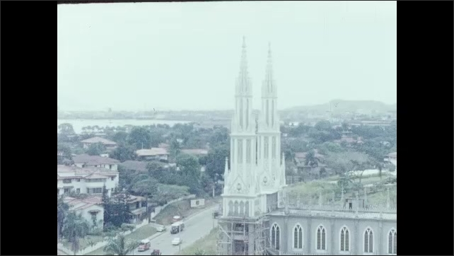 1950s: City, buildings, water. Church spires, cars drive down road. Women sit in booth at restaurant. Palm tree.
