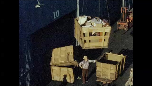 1950s: Men unload crate of luggage from ship. Dock workers receive crate. Classical stone building.