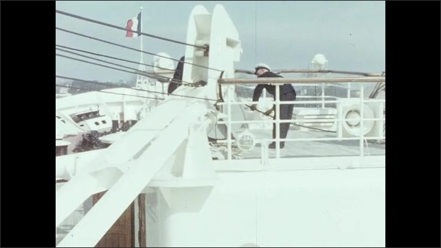 1950s: CARIBBEAN: sailors on deck of ship. Crew busy on deck. Passengers on deck. Ship leaves wharf