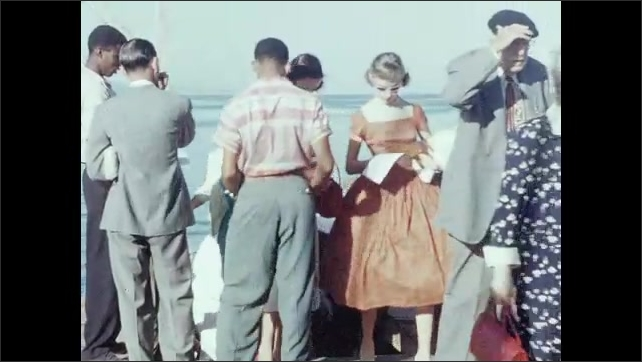 1950s: CARIBBEAN: men row boat at sea. Passengers arrive on land from sea. Passengers look at paper guides.