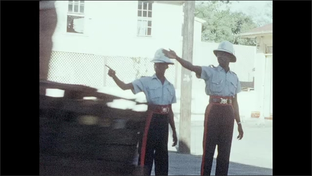 1950s: CARIBBEAN: men in uniform. Traffic police in street. Horse and cart in street.