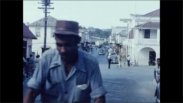 1950s: CARIBBEAN: man rides bicycle through town. View along road through town. People in town. Car drives around traffic police.