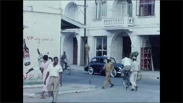 1950s: CARIBBEAN: pedestrians walk in town. Horse and cart in town. Man rides bicycle in town. Paintings on walls outside shops.