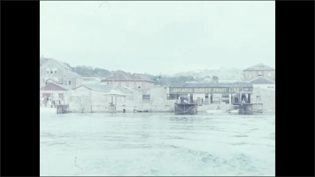 1950s: Boys and teens splash and swim in the ocean. Warehouses and buildings hug docks on bay.