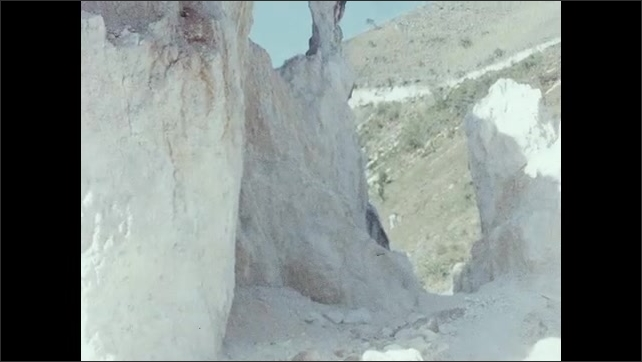 1950s: Rocky cliff and cave entrances. House overlooks hills and valleys.