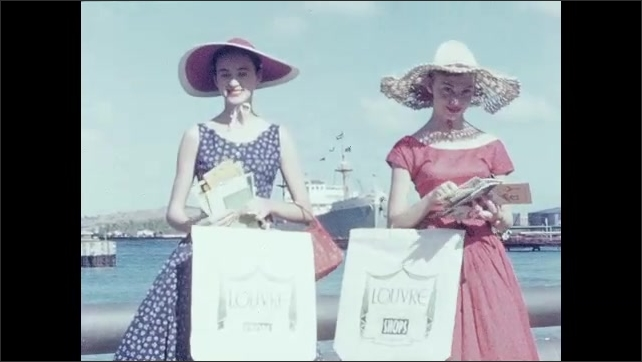 1950s: Tourists walk along docks near large cruise ship. Banners wave in breeze on large ocean cruise ship. Girls in sun hats flip through postcards on deck of ship.