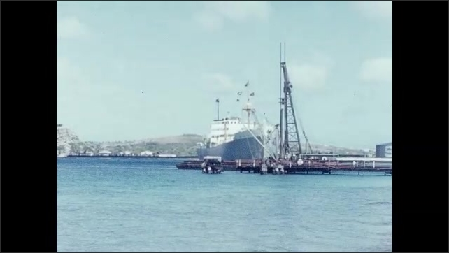 1950s: Cruise ship sits in bay near oil drilling platform. Drill moves up and down on oil drilling platform.
