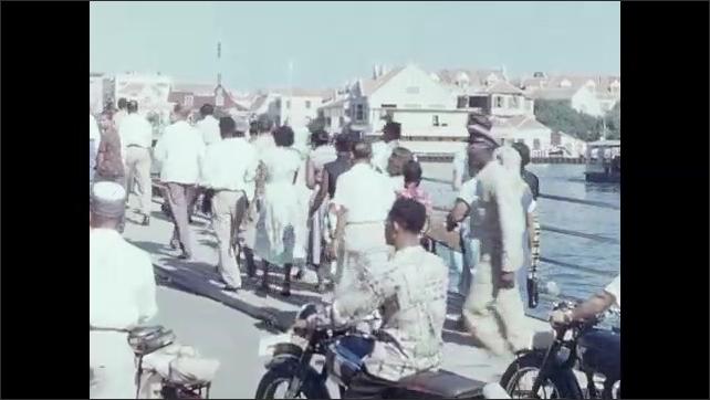 1950s: Man lifts gate to bridge. Pedestrians and men on motorbikes cross bridge. Cars and pedestrians cross bridge. Woman and girls walk through parking lot.