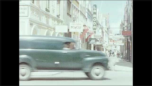 1950s: People walk around city, cars drive down street.