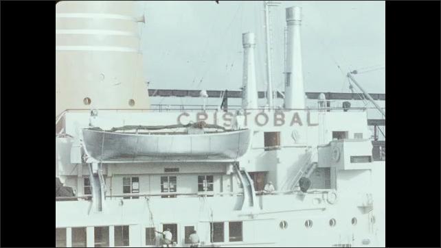 1950s: Men load items onto ship.