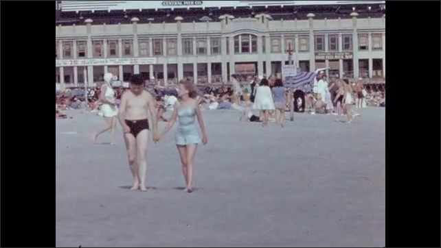 1940s: Two women walk on the beach, man and woman hold hands, several people in background. Woman runs on the sand and jumps.