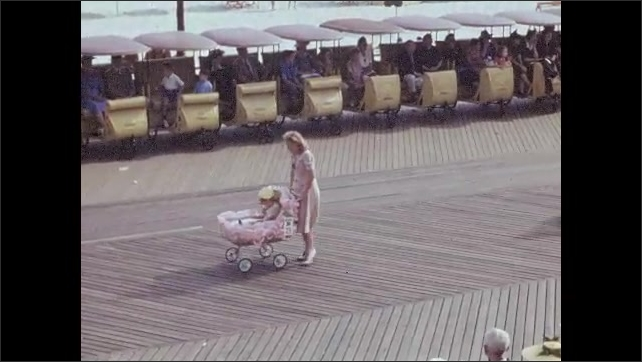 1940s: Girls' marching band walks in parade. Women walk with children in strollers, carts and floats in parade.