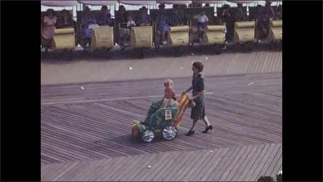 1940s: Three costumed girls dance in parade. Man pushes cart with a big rose. Women push parade floats with children on them. Women push strollers with children in parade, people watch and clap.