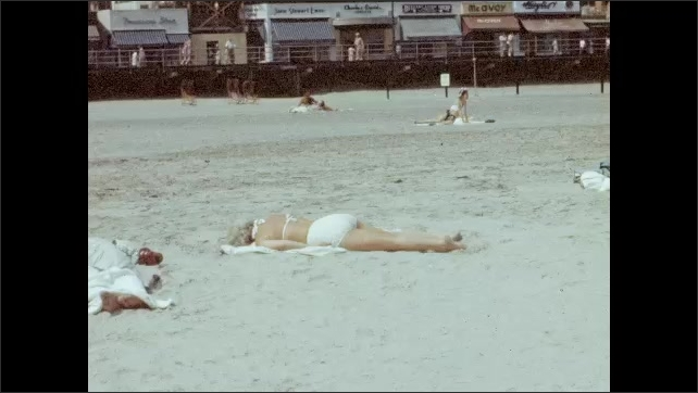 1940s: Lifeguard sits in high chair and another lifeguard stands on the beach, Atlantic City in background. Woman lays on the beach. People walk along the beach. Zeppelin flies from right to left.
