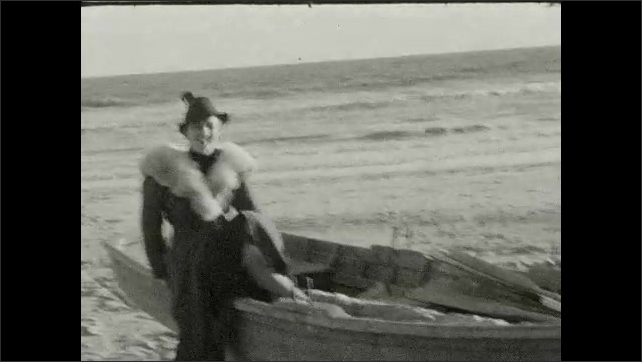 1940s: UNITED STATES: lady stands by boat on beach. Lady n beach. Man walks on beach by pier. Lady poses for camera. Man poses for camera.