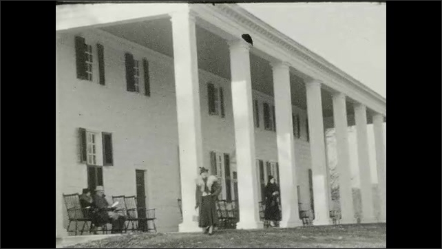 1940s: UNITED STATES: view across garden to house. Lady stands by building and columns
