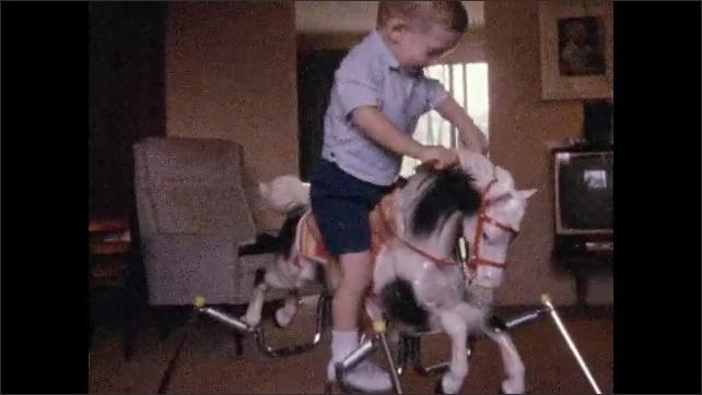 1970s: Little boy climbs onto rocking horse, rides rocking horse.