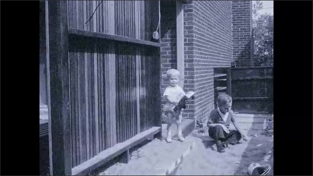 1970s: Toddler plays outside with toy car. Boy plays in sandbox. Toddler brings car into sandbox.