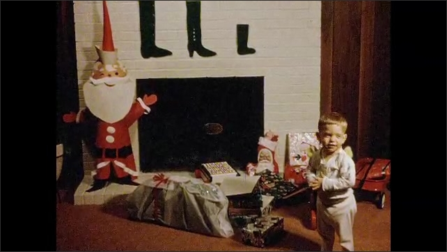 1970s: Little boy walks into living room, looks at Christmas presents.