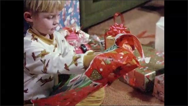 1970s: Christmas tree. Boys walk around corner, run to Christmas presents. Boys sits on floor, open presents.