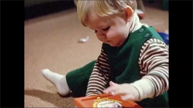 1970s: Boy sits on floor, plays with train set, talks. Toddler sits on floor, plays with Jack in the Box.