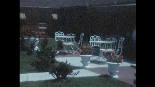 1950s: View of swimming pool with croquet sit at edge. Patio tables.