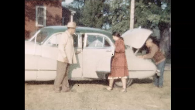 1950s: People place luggage in car. Woman climbs into car. Car drives alongside body of water with boat hugging shore.