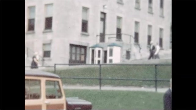 1950s: Open-air vehicle with people seated atop drives down street. People walking and standing outside large building.