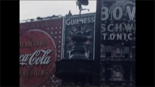1950s: Lighted signs on buildings in Piccadilly Circus. People sit at fountain in center of Piccadilly Circus. People cross bust street near Provincial Bank.
