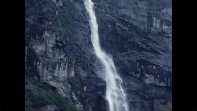 1950s: EUROPE: waterfall on rocks. Snow on mountain summit