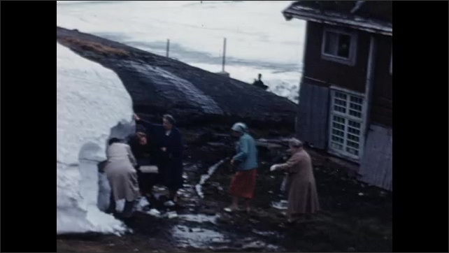 1950s: EUROPE: NORWAY: Frozen Lake of Djupvand. House by snow. Man takes photo. People look at snow.