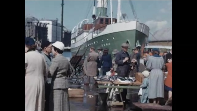 1950s: EUROPE: NORWAY: Fish dropped in water. Bergen fish market. Man weighs fish for tourists. Lady smiles at camera