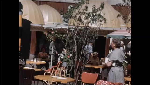 1950s: EUROPE: NORWAY: Outdoor restaurant. Bergen, Norway sign. Lady sits on table outdoors.