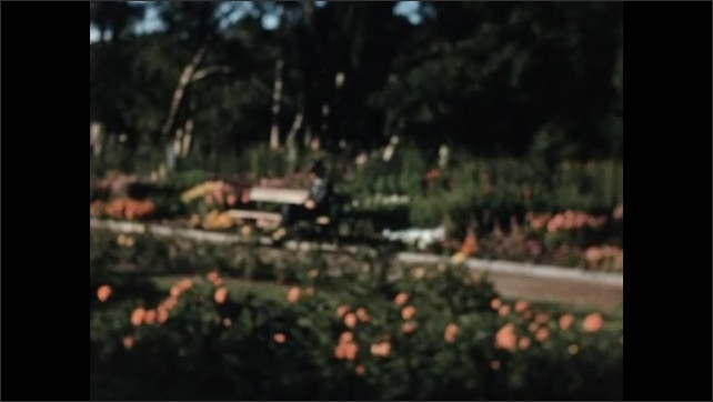 1950s: EUROPE: NORWAY: Ladies visit Palace gardens. Fountain in gardens. Lady in traditional dress.