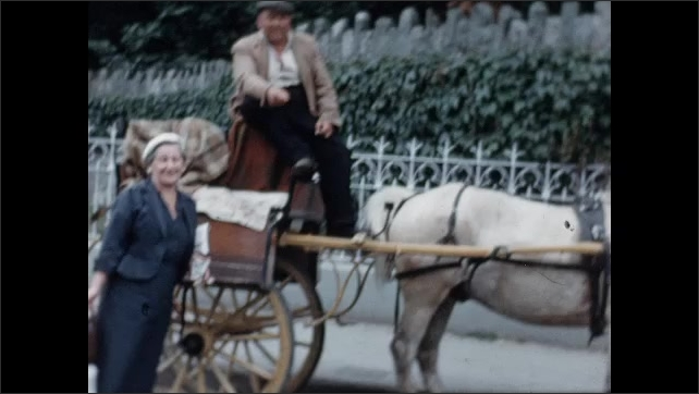 1950s: Woman and man pose by horse carriage. Men and women on and near horse carriages. Horse carriages and cars line street.